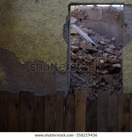 Hole in ragged stone wall of old abandoned brockn building with wooden fence full with messy garbage ruined house depressive gloomy mood on natural baclkground outdoor, square picture - stock photo