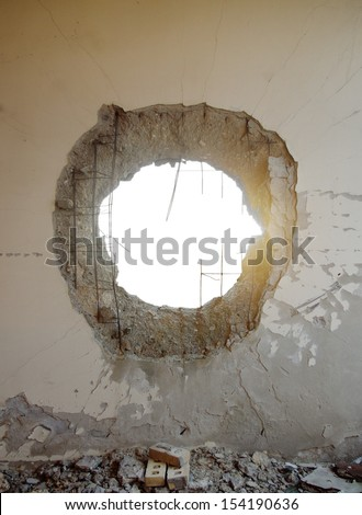 Hole in the concrete wall from tank shell with isolated space  - stock photo