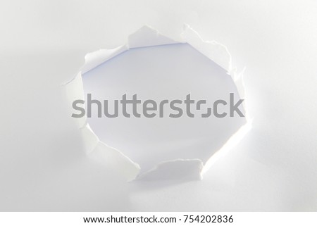 Hole in the sheet of paper with torn sides , Ripped hole in sheet of paper , Copy space for text or promotion.