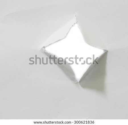 hole in white paper. - stock photo