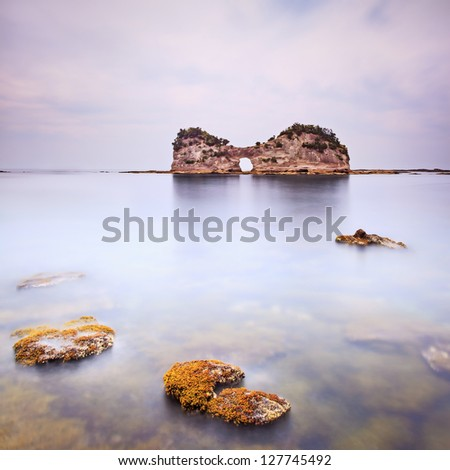 Hole island and rocks in a tropical blue ocean. Cloudy sky. Long exposure photography - stock photo