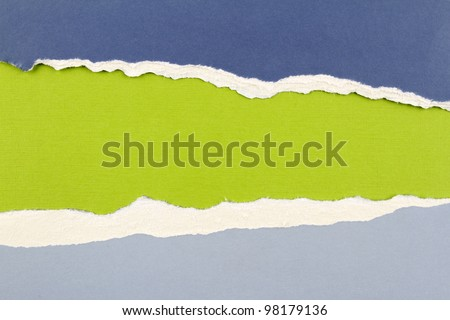 Hole ripped in blue paper on green background. Copy space - stock photo