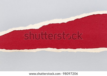Hole ripped in blue paper on red background. Copy space - stock photo