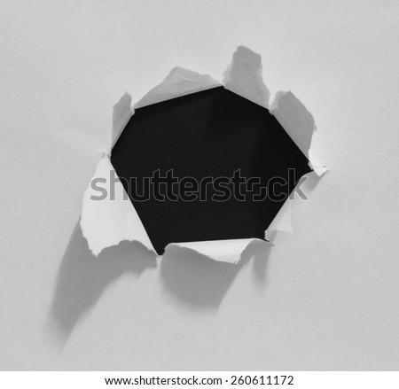 Hole ripped in paper on black - stock photo