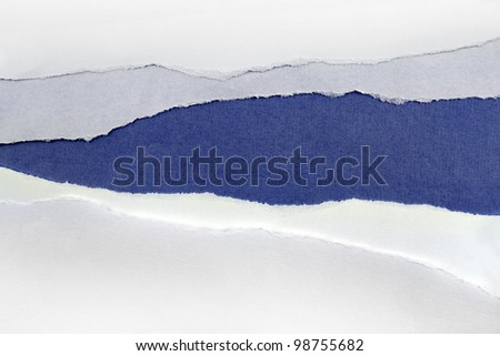 Hole ripped in white paper on blue background - stock photo