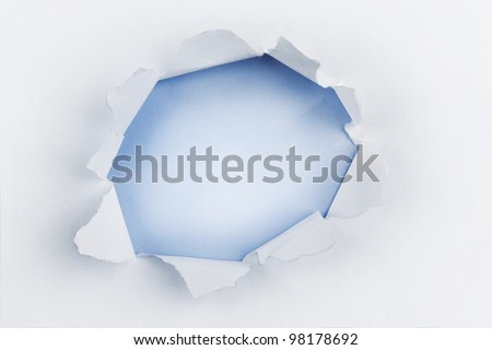 Hole ripped in white paper on blue background. Copy space