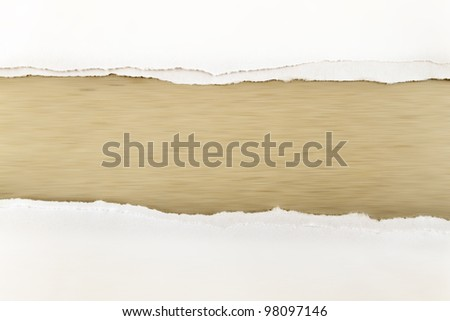 Hole ripped in white paper on brown background. Copy space - stock photo