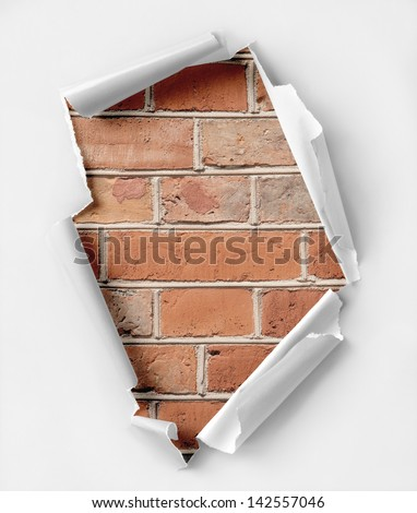 Hole ripped paper. Brick wall background. - stock photo