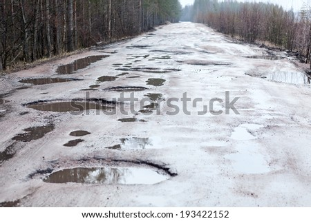 Holes and puddles on bad broken road - stock photo