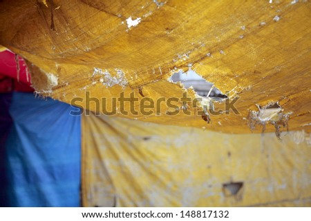 Holes in booth ceilings, Indian market - stock photo
