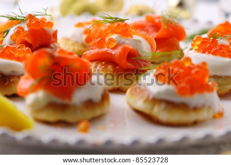 Holiday appetizer with caviar and salmon on white plate - stock photo
