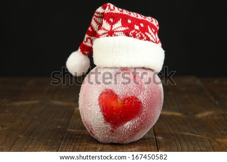 Holiday apple with frosted heart on wooden table on black background - stock photo