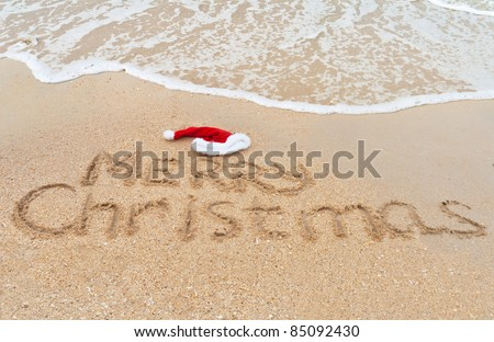 Holiday background - Merry Christmas written on tropical beach sand - stock photo