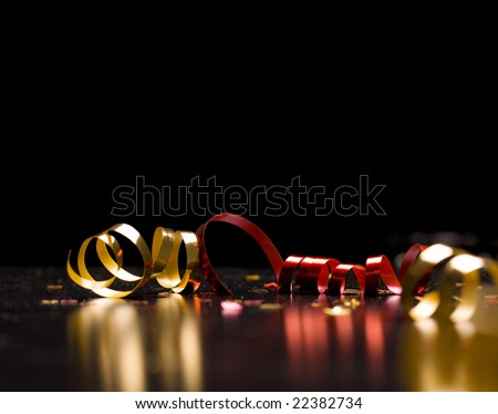 Holiday background; ribbons on black - stock photo