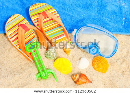 Holiday background. Seashells and diving mask on the beach - stock photo