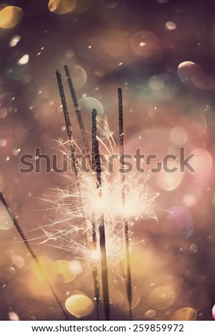 Holiday background with bright bengal fire and colorful bokeh lights. - stock photo