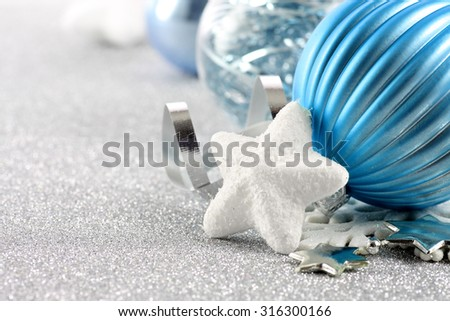 Holiday background with white snowflake and blue Christmas ornaments Christmas or holiday background with a white snowflake and blue ornaments on a silver glitter background  - stock photo