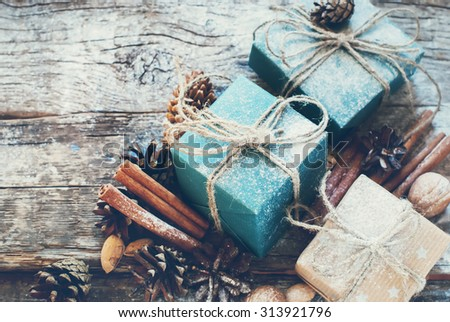 Holiday Boxes with Linen Cord, Cinnamon, Pine cones, Nuts. Natural Gifts on Wooden Background. Toned - stock photo