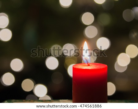 Holiday candle with bokeh white lights