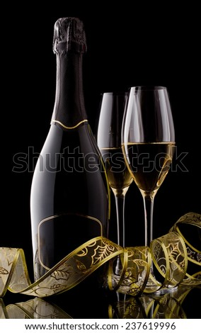 Holiday champagne bottle and two champagne glass on a black with decoration ribbon. - stock photo
