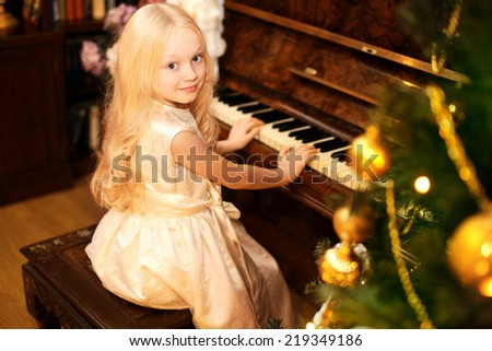 Holiday, christmas and people concept - pretty little girl with piano - stock photo