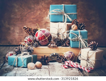 Holiday Christmas Gifts with Boxes and Natural Twine, Balls, Pine Cones, Wallnuts, Fir Tree Toys on Wooden Background. Toned image - stock photo