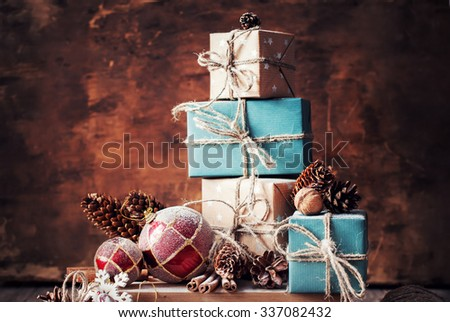 Holiday Christmas Gifts with Boxes, Twine, Balls, Pine Cones, Walnuts, Fir Tree Toys on Wooden Background - stock photo