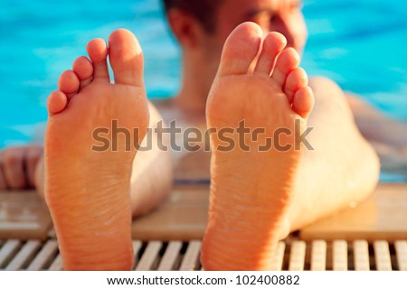 Holiday concept with man soaking feet in swimming pool. - stock photo
