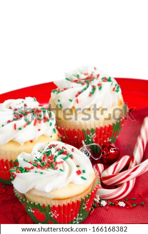Holiday cupcakes with vanilla frosting and red and green sprinkles, served on a red holiday plate on white background with copy space. Shallow depth of field. - stock photo