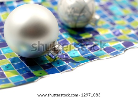 Holiday decoration ornaments resting over wrinkled used torn wrapping paper on white background - stock photo
