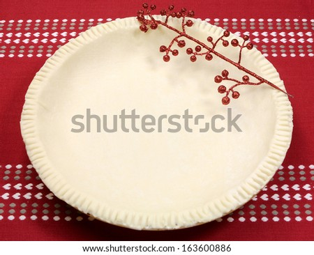 Holiday festive baking with an empty pie shell pastry crust with festive decoration on red and white cloth. - stock photo