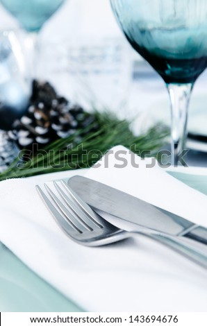 Holiday function event table setting with blue silver white christmas theme, cutlery wine glass and napkin - stock photo