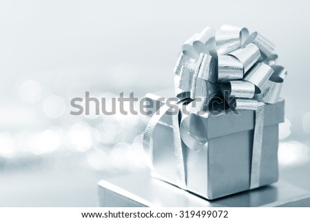 Holiday gift in silver box decorated with ribbon and bow - stock photo