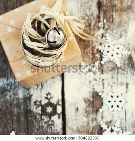 Holiday Gift with Jingle Hand Bell and Natural Twine on Wooden Snow Background. Toned image - stock photo