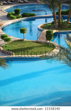 Holiday hotel and open air resort style swimming pool - stock photo