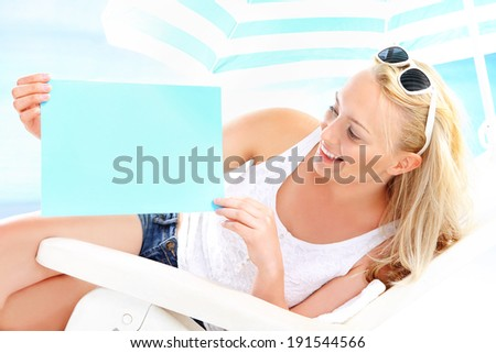 Holiday on the beach - space for your text  Beautiful blonde woman sitting on a lounger beach holding a blue sign with space for text.  - stock photo