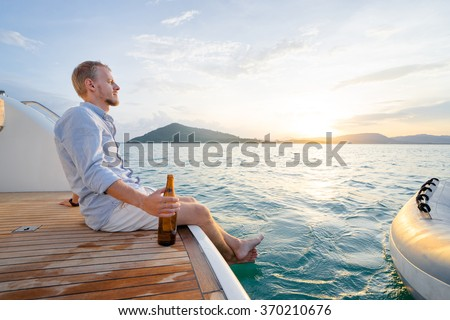 Holiday on the sea. Relaxed young man with beer bottle sitting on the yacht deck.