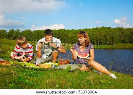 holiday outdoor portrait of happy families eating watermelon at the picnic near camp tent - stock photo