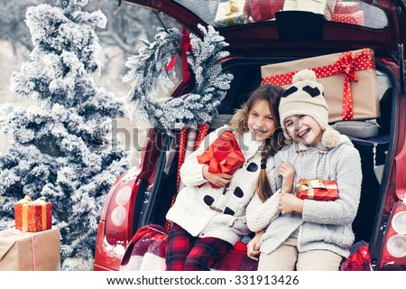 Holiday preparations. Pre teen children enjoy many Christmas presents in car trunk. Cold winter, snow weather. - stock photo