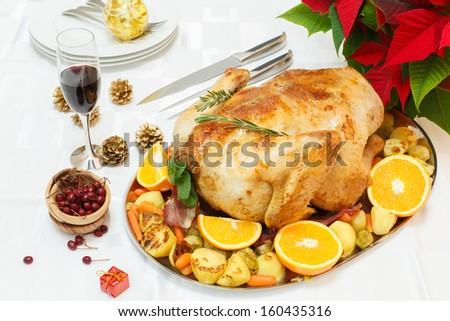 Holiday roasted turkey. A festive roasted turkey on a platter with an assortment of vegetables, fruit and spices - stock photo