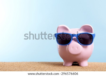 Holiday savings, summer travel money concept, piggybank sunglasses.  Copy space.