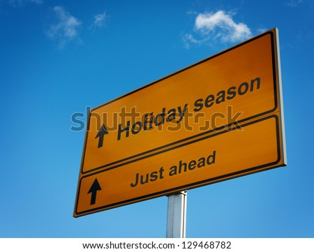 Holiday season just ahead road sign background sky.