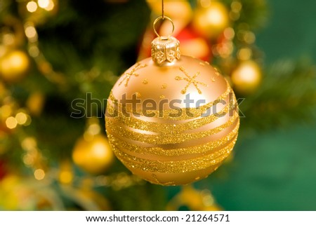 Holiday series: golden Christmas ball with fir  in green background