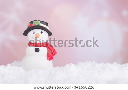 Holiday snowman figurine on snow with colorful background - stock photo