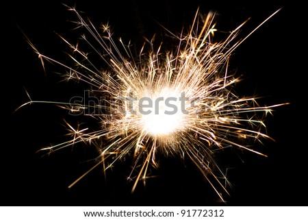 Holiday sparkler over black background - stock photo