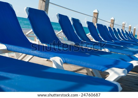 Holiday sun loungers lined up at the seaside - stock photo