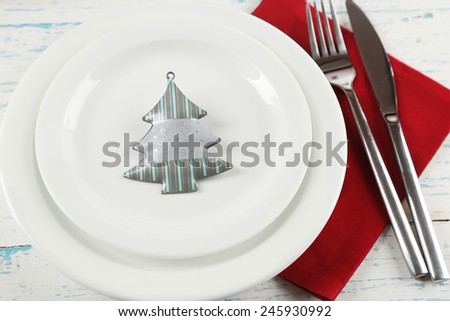 Holiday table setting with Christmas decoration on color wooden background