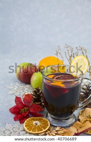 Holiday tea in a clear glass surrounded by fruit on blue background