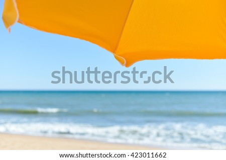 Holiday view of sun umbrella, sandy beach and ocean shore background outdoors - stock photo
