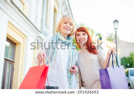 Holiday with mother. Family shopping. Outdoor portrait of smiling caucasian middle aged woman and her adult daughter holding bags. - stock photo